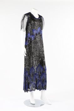 A sequined tulle flapper dress, early 1920s, ankle length, the black tulle ground covered with black sequins, with bands of electric blue beaded palmettes, tulle sleeves. Front