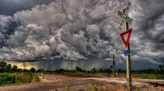 railroad crossing under stormy skies hdr
