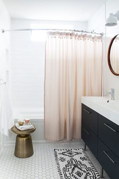 One way to dress up a neutral or black + white bathroom is with nothing more than a blush pink shower curtain. A pop of unexpected color can go a long way in adding personality to your shower space.