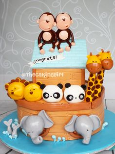 Cute Noah's Ark Baby Shower cake! Adorable Noah's Ark fondant animal figurines - giraffes, elephants, pandas, lions, monkeys cake ideas. www.thecakinggirl.ca