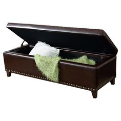 """Storage bench with a tufted cushion top and nailhead-trimmed upholstery. Product: Storage bench Construction Material: Hardwood and upholsteryColor: BrownFeatures: Ideal for extra seating, storage or resting your feetDimensions: 16"""" H x 51"""" W x 19.25"""" D"""