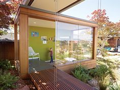 Luc gets creative in the tearoom, which includes a small play area for the children. The walls of the space exemplify the simplicity of the new structures: Electrical and lighting components are run through the ceiling and floor, leaving many exterior walls unencumbered and free to hold floor-to-ceiling windows. On the raised platform is a Soleil lounge chair by Emu.  Photo by: Caren Alpert