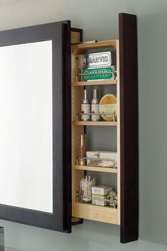 A framed bath mirror that has more than good looks to its credit - a hidden pullout, perfect for small bathroom storage.