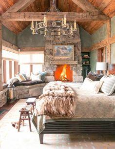 romantische-schlafzimmer-landhausstil-chaler-naturstein-kamin-fell-bettdecke