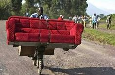 This man makes his living with a red couch mounted on the front of his bicycle to taxi tourists around.