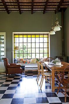 Cocina campestre y moderna con gran ventanal de vidrio repartido, rincón de sobremesa y mesa con sillas tipo Thonet.