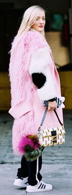 Shaggy pink faux fur coat worn with black pants and white and black adidas