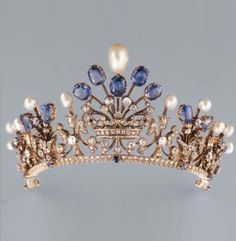 AN ANTIQUE PEARL, SAPPHIRE AND DIAMOND TIARA, CIRCA 1880. Designed as five graduating pearl and sapphire-set sprays and diamond-set scroll motifs, centring on a diamond-set marquise's coronet, mounted in silver and gold, with six brooch fittings, five hairpin fittings and a screwdriver, each spray and coronet detachable, in fitted maroon leather Auger case stamped with a count's coronet.