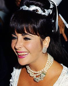 Here she is wearing the Elizabeth Taylor Double-Headed Lion Necklace (1965) that she and Richard Burton designed with David Webb. She has it doubled around her neck. SEE related pin.
