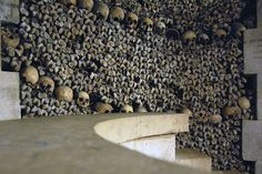 Deep in the Catacombs of Paris the bones and skulls are stacked neatly in this chamber. The entrance to the Catacombs is in the 14th Arrondissement at Place Denfert. The catacombs are a network of about 186 miles (about 1 mile is open to the public) of subterranean tunnels and rooms located in what were Roman-era limestone quarries.    Burial use in these empty quarries began in 1786 because the Les Halles district of Paris was suffering from disease, due to the contamination caused by…