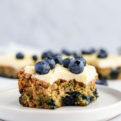 Gorgeous lemon blueberry zucchini cake bursting with juicy blueberries and topped with a luscious lemon buttercream frosting. This easy, gluten free blueberry zucchini cake is made with a mix of oat and almond flour and naturally sweetened with honey. A delicious snacking cake perfect for using summer produce! #zucchinirecipe #zucchini #cake #glutenfree #baking #dessert #lemon #blueberries