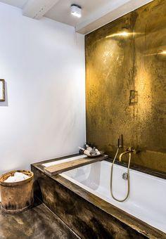 Badeværelse med badekar og bagvæg lavet i tombak der ligner guld