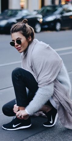 Maja Wyh is wearing a grey fluffy sweater from Dorothee Schumacher, grey silk scarf from Vyvyn Hill By Maja, jeans from Set Fashion and the trainers are from Nike