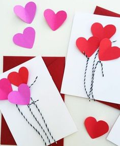 two white cards, decorated with pink and red heart shapes, and black and white thread, placed over two red envelopes, more pink and red heart shapes nearby