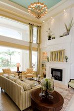 living room, blue-green ceiling, 2 story tall window treatments, wainscotting, crown moldings, large chandelier