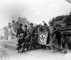 """US soldiers celebrate with a captured German flag in front of a destroyed Panther tank. The group of infantrymen were left behind to """"mop-up"""" in Chambois France last stronghold of the Germans in the Falaise Gap area"""