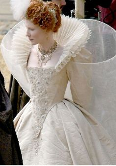Queen Elizabeth makes us envious in her show of power and desirability through her hair and elegant white dress.