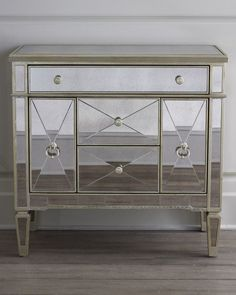 """<ul> <li>Mirrored chest made of hardwood solids, then covered with mirrors.</li> <li>Antiqued silver finish with antiqued gold-painted accents.</li> <li>Five drawers.</li> <li>36""""W x 19""""D x 35""""T.</li> <li>Imported.</li> </ul>"""