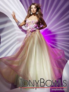 Tony Bowls Paris Style 112756  Strapless satin and tulle ball gown with ruffled tulle sweetheart neckline, hand-beaded appliquéd bodice with exaggerated asymmetrically dropped waist and large bow on natural waistband, gathered tulle skirt. Removable straps included.