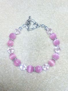 I created this Bracelet using 8mm Glass Faceted Pink Cat's Eye Rounds 8mm Glass Pink Bicones 11/0 Delica Silver Lined Seed Beads 4mm SP Rounds Silver Tone Metal Heart Toggle Clasp Total length from en