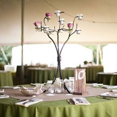 A nature-inspired tablecloth and rustic wooden table number coordinates beautifully with the simplicity of this candelabra centerpiece.Photo Credit: Honey Heart Photography