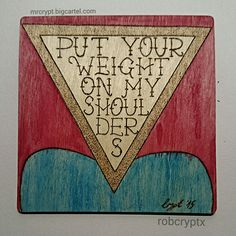 """Pyrography and watercolour plaque referencing Enter Shikari lyrics from Dear Future Historians (off The Mindsweep). Quote reads """"Put your weight on my shoulders"""" and features the upturned triangle symbol."""