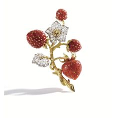 PROPERTY FROM THE ESTATE OF MRS. WALTER MATTHAU: 18K Gold, Platinum, Diamond and Coral Strawberry Clip-Brooch, Donald Claflin for Tiffany & Co., Circa 1970. The meandering textured gold stems supporting carved coral strawberries studded with gold seeds, accented by a flower and leaves set with round diamonds weighing approx 4 carats.