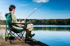 fishing: Man fishing at lake sitting on jetty close to the water