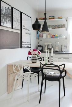 Sometimes beauty and harmony come from asymmetric interiors. Take this kitchen as a good example -unpaired metal chairs, wooden table and an unequal gallery wall.