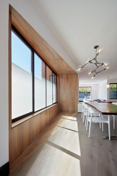 The windows that sit on the side of this modern house are partially opaque, providing privacy but at the same time allowing the light to shine through.