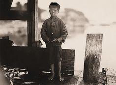 Hiram Pulk (9 años) trabaja en una Empresa Conservera de Marisco, hace 5 cajas por día y le  pagan unos 5 centavos de dólar por caja.                                                   Eastport-Maine.