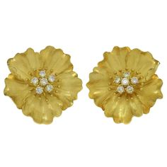 """Tiffany & Co. Alpine Rose Diamond Yellow Gold Clip-on Earrings. These magnificent Alpine Rose earrings by Tiffany & Co. are crafted in the shape of five-petal flowers and feature sparkling centers prong-set with brilliant-cut round F-G VVS2-VS1 diamonds of an estimated 0.75 carats, set in 18k yellow gold. Completed with omega backs for both pierced or non-pierced ears. Measurements: 1.06"""" (27mm) length."""