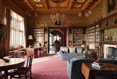 The Library at Knightshayes Court, Devon. Bookcases in the Gothic style with linenfold paneling by John Crace.