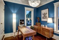 Blue walls, modern walnut furniture, and classic white trim give this home office a contemporary-yet-classic feel. Office Color Schemes, Home Office Colors, Living Room Color Schemes, Home Office Design, Home Office Decor, House Design, Home Office Paint Ideas, Office Ideas, Transitional Living Rooms
