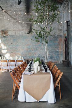 Industrial reception ideas | brown paper table runner + black glass bottle place settings | photo by Flora and Fauna
