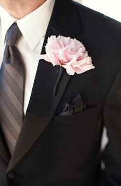 A groom's gray tie and black pocket square are set off by a light pink boutonniere. #Weddings #Groom