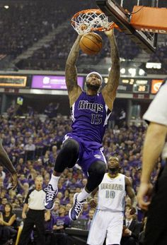 Sacramento Kings center DeMarcus Cousins (15) dunks as Denver Nuggets point guard Nate Robinson (10) watches during the second quarter of an NBA basketball game Wednesday, Oct. 30, 2013, in Sacramento. (AP Photo/Genevieve Ross)