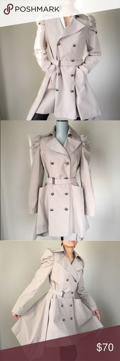 """Ultra chic trench coat with waist cinch belt. New well tailored chic trench coat. Modern classic with a dash of drama. Princess pleated shoulder . Two front pockets. Fully line with soft and silky fabric.hem hangs longer on the side ; the signature unique style. Brand new tag line still attached to the belt. Shoulder 14"""", bust 19"""", length 33.5"""" front , side back 36"""". Sleeve 25"""" waist:16.5"""" hips 24"""". All measurements are taken flat lay. Color light tan Follow me on INSTAGRAM: @chic_bomb and…"""