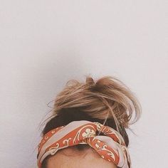 A messy top knot paired with a printed headscarf.