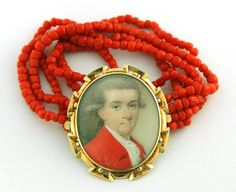 Miniature of a gent known as Henry Norreys of Davyhulme, with powdered hair en queue, wearing a red jacket with white stock and cravat.  Watercolour on ivory, English School C1765.  Gold bracelet frame with decorative edging, the reverse engraved with sitter's details, attached to 5 strings of coral beads.