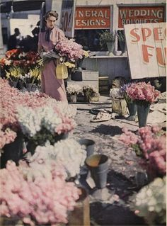 A lovely image of a 1940s woman shopping for flowers that just happen to match her dress perfectly. #vintage #fashion #dress #pink #flowers #1940s