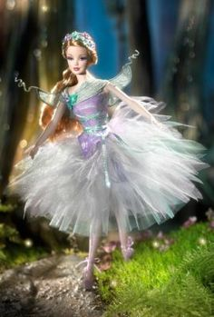 Barbie® as Titania. Inspired by one of Shakespeare's most beloved plays, A Mid-Summer Night's Dream, Barbie® doll as Titania, Queen of the Fairies is a fantasy in a violet + teal cloud of tulle. The bodice is made of lavender pleated organza that drapes off the shoulder fastened with flowers. As befits the Fairy Queen, Barbie® wears her long blond hair pulled back with a wreath of flowers as a crown + long ringlets down back and shoulders.
