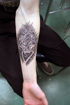 Awesome wolf behind tree branches forearm tattoo