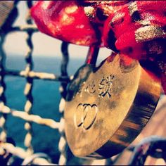 Cross the overpass, street-sellers by the roadside. Sellin' locks with keys, bright gold. We're sold. Oh. Etched in our names to make it our own. Locked it on a fence to make it known.  Love lock on The love route at #5terre