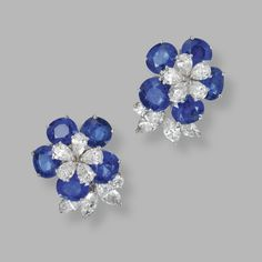 PAIR OF 18 KARAT WHITE GOLD, SAPPHIRE AND DIAMOND FLOWER EARCLIPS Designed as flowerheads set with oval sapphires weighing 12.34 carats, and pear-shaped, marquise-shaped and round diamonds weighing approximately 4.40 carats.