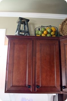 Wire basket filled with faux lemons and limes on top of the kitchen cabinet