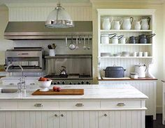 white farmhouse style kitchen with glass front cabinets, walnut