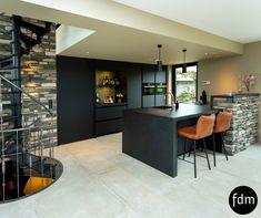 Deze moderne, strakke en zwarte Fenix keuken met graniet aanrechtblad komt prachtig tot zijn recht bij de stenen muren.