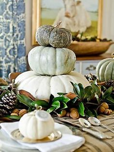 Memorable Thanksgiving Table    Stacked Pumpkins This is a simple alternative to the default flower arrangement.  Stack three pumpkins (live or artificial) from largest to smallest as the centerpiece.  Use pumpkins that are the same color or in varying shades as I did here.  Tuck in greenery, like magnolia leaves, as well as nuts and pine cones around the base.