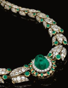 EMERALD AND DIAMOND NECKLACE, LATE 19TH CENTURY Set at the centre with a cabochon emerald bordered with circular-cut diamonds and kite-shaped emeralds, continuing to a series of graduated stylised lotus links set with rose, oval, single- and circular-cut, cushion and pear-shaped diamonds and circular-cut emeralds.